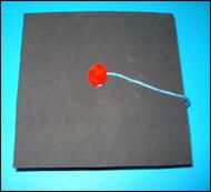 Collez un bout de laine d'environ 10 cm sur le dessus du carré, au centre.
