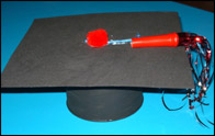 Attachez la flute avec la laine pour compléter votre chapeau de finissant.