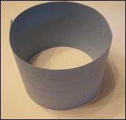 6. Pendant que les enfants collent leurs boules de ouate, coupez leur papier décoré en deux sur la longueur.