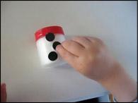 Pendant que les enfants font cela, découpez de petits ronds noirs pour les boutons, un demi-cercle noir pour la bouche et un triangle orange pour le nez.