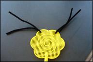 Enfilez deux cure-pipes noirs dans le haut de la tapette à mouches pour représenter les antennes.